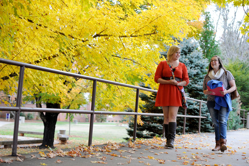 female students walking in the fall on campus